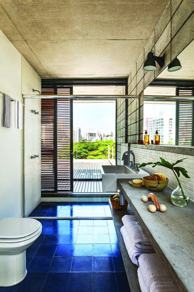 banheiro com ladrilho azul e bancada de cimento